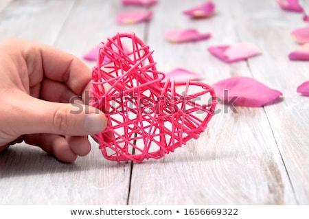 Coração pétalas mesa de madeira mãos belo velho Foto stock © jarin13