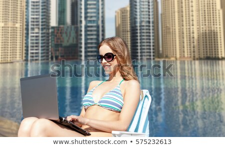 smiling young woman with sunglasses over city pool Stock photo © dolgachov