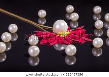 white pearls necklace over red petals on black stock photo © manaemedia