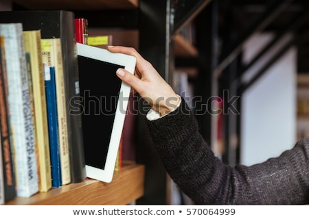 Women hand taking tablet computer from a bookshelf Stock photo © deandrobot
