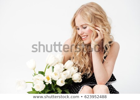 Pleased Blonde woman sitting on floor with bouquet of flowers Stock photo © deandrobot