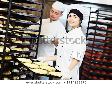 Happy young baker holding tray of bread. Stock photo © RAStudio