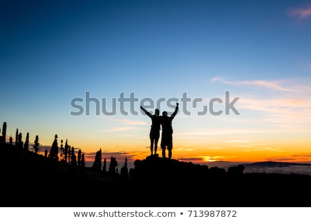 teamwork couple climbing and reaching mountain peak stock photo © blasbike