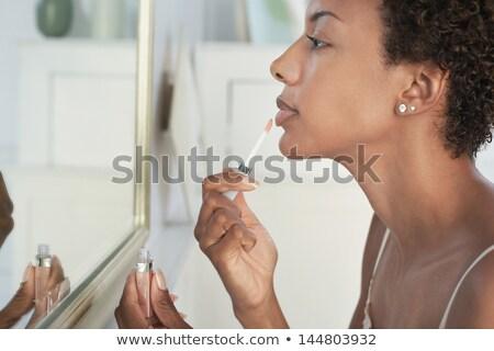 Woman applying lipstick in the morning Stock photo © Kzenon