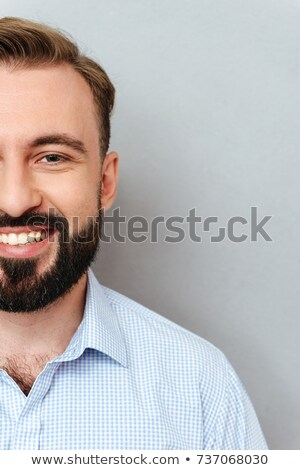 Half face of smiling bearded man in business clothes Stock photo © deandrobot