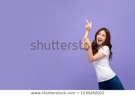 Happy young beautiful woman pointing. Looking aside. Stock photo © deandrobot