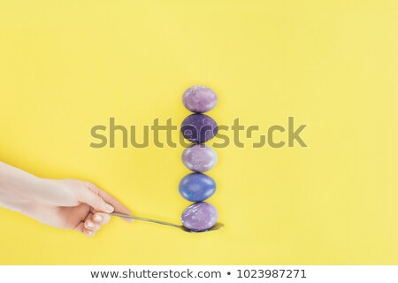 cropped view of woman holding spoon with row of painted eggs for easter isolated on yellow stock photo © lightfieldstudios