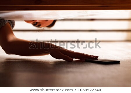 Someone is hiding a smartphone under the bed Stock photo © Nobilior