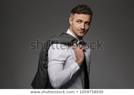 Image of caucasian businessman 30s in suit smiling and holding f Stock photo © deandrobot