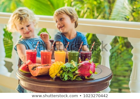 children boy and girl drink orange smoothie from papaya stock photo © galitskaya
