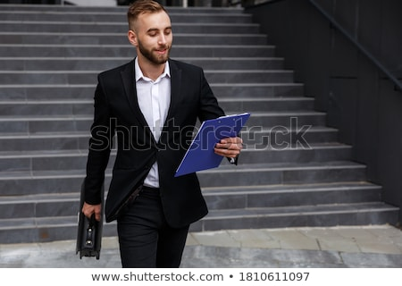 cheerful businessman dressed in shirt walking outdoors stock photo © deandrobot