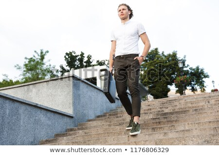 Full length image of Calm curly business man with briefcase Stock photo © deandrobot