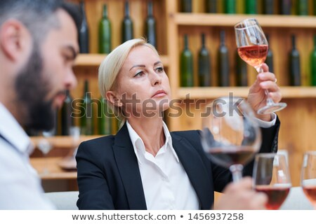 Confident blonde female sommelier or cavist looking at color of wine Stock photo © pressmaster