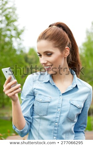 Happy young woman with toothy smile holding camera in front of her Stock photo © pressmaster