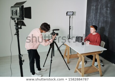 Young cameraman bending in front of video shooting equipment in studio Stock photo © pressmaster