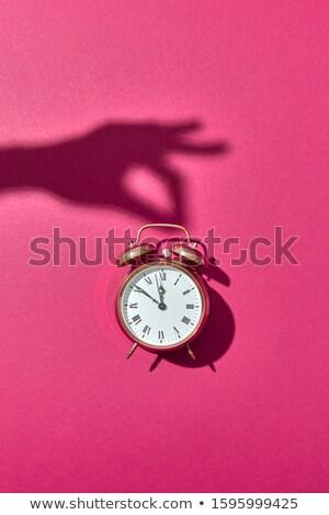 Shadow from hand holdes alarmclock. Stock photo © artjazz
