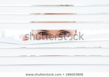 Blond woman peering through window blind Stock photo © photography33