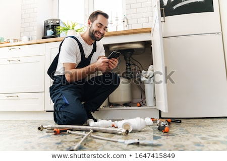 Stock photo: Plumber on the phone
