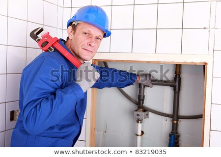 Stock photo: Experienced plumber using a large wrench in a bathroom