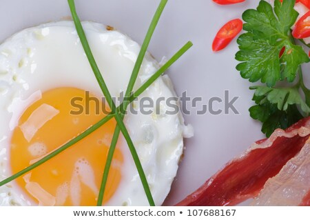 Stok fotoğraf: Fried Eggs Sunny Side Up With Bacon Parsley And Lettuce