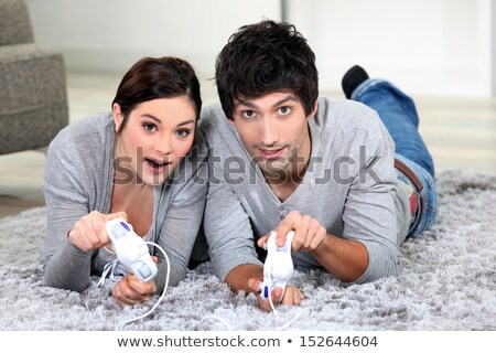 Couple laying on rug playing video games Stock photo © photography33