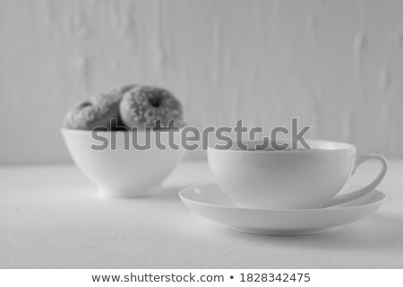 Doughnut with multi coloured icing sugar and a cup of coffee with a spoon on white plates against a  Stock photo © wavebreak_media