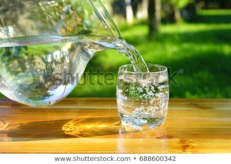 Stock photo: Pouring Water into a Glass against the Green Background