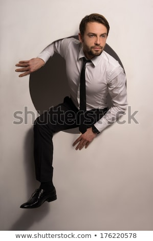 businessman climbing out of a circular hole stock photo © stryjek