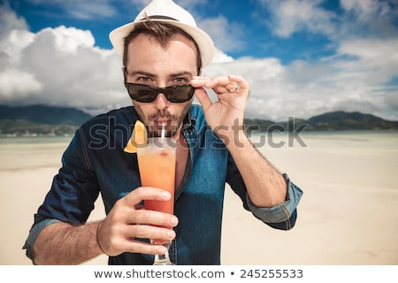 casual man with hat taking off his sunglasses stock photo © feedough