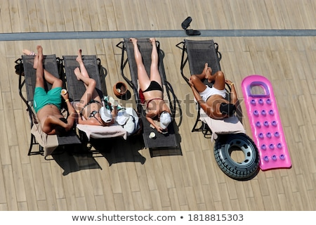 Four friends sunbathe on the sun loungers on the beach Stock photo © Geribody