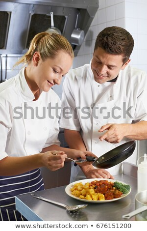 Chef Instructing Trainee In Restaurant Kitchen Stock photo © HighwayStarz