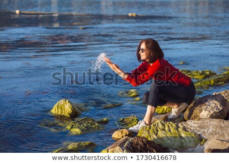 Young woman sprinkles by water on beach on sunset Stock photo © Paha_L