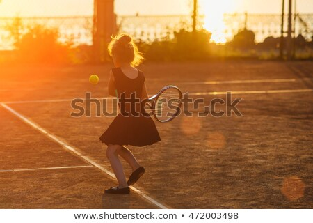 girl playing tennis at sunset stock photo © adrenalina