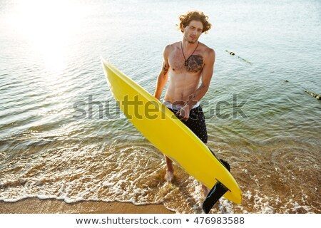Young curly man with surf board standing in the ocean Stock photo © deandrobot