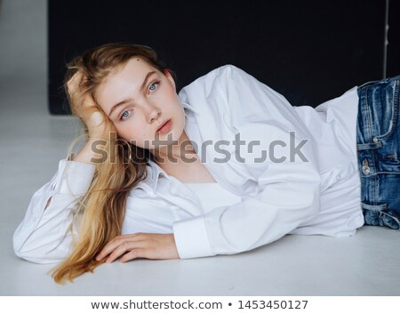 attractive woman in white shirt lying in bed stock photo © deandrobot