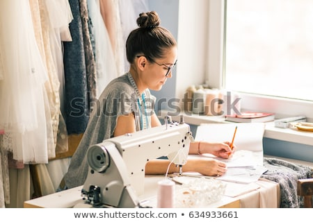 hands woman tailor working cutting a roll of fabric on which she stock photo © yatsenko