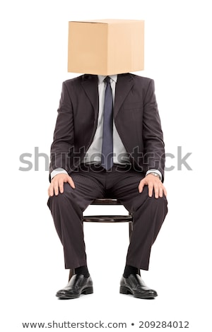 man in suit sitting on box stock photo © deandrobot