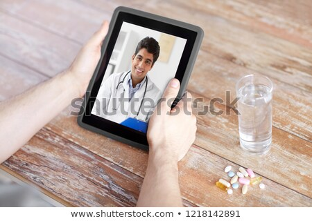 close up of hands with tablet pc pills and water stock photo © dolgachov