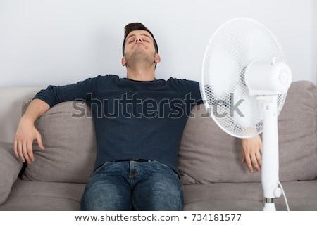 Homme séance canapé refroidissement fan Photo stock © AndreyPopov
