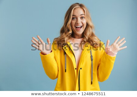 Image of excited woman 20s wearing yellow raincoat laughing at c Stock photo © deandrobot