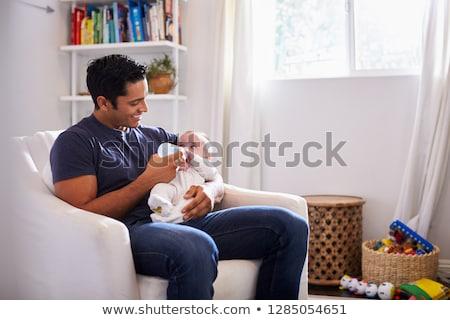 close up of father feeding baby from bottle stock photo © dolgachov