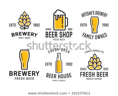 Cold bottle and glass of craft beer on old barrel Stock photo © DenisMArt