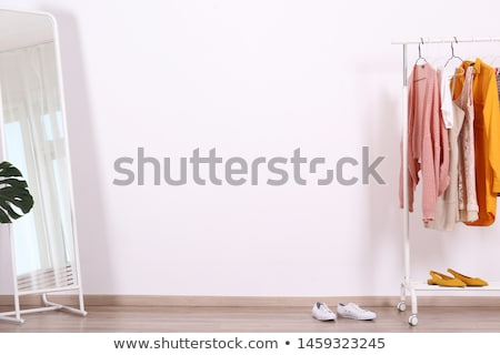 Stock photo: woman with dress at vintage clothing store mirror