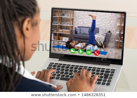 Businesswoman Doing Video Calling With Yoga Trainer Stock photo © AndreyPopov