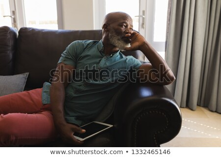 Side view of a thoughtful senior man using digital tablet on a sofa while looking away in living roo Stock photo © wavebreak_media
