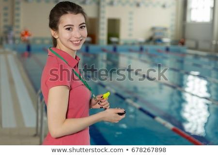 Jovem profissional treinador assobiar olhando cronômetro Foto stock © pressmaster