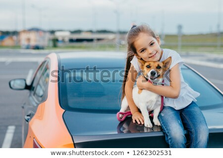 Small attractive female child embraces her favourite dog, sit together at trunk of car, have rest af Stock photo © vkstudio