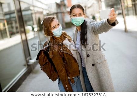 Bastante mulheres jovens máscara rua dois telefone móvel Foto stock © boggy