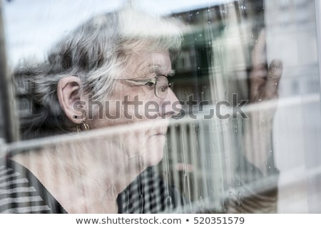 Senior Woman Looking Out Through A Window Like Depress Zdjęcia stock © Lopolo