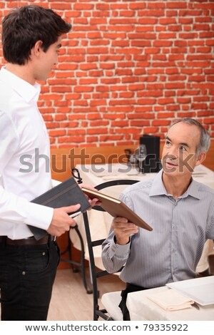 young waiter serving lunch to an older customer stock photo © photography33